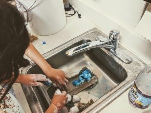 Two students put their clay landfill in a sink for testing. They begin by filling the engineered landfill with dye soaked cotton balls. The more cotton balls they can fit in their landfill, the higher their point score is.