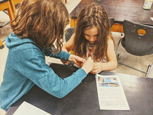 two students work together with a lab book in front of them. Students are working to build their environmental engineering solution to oil spills