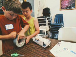 egg drop science experiment using duct tape, boys working together to engineer egg capsule