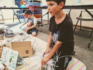 egg drop science project recycled materials boy working on egg drop engineering