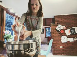 how to make fluffy slime - girl making slime with hairspray in silver bowl