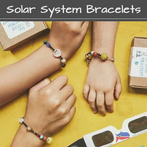 solar system bracelet on kids hands for science project