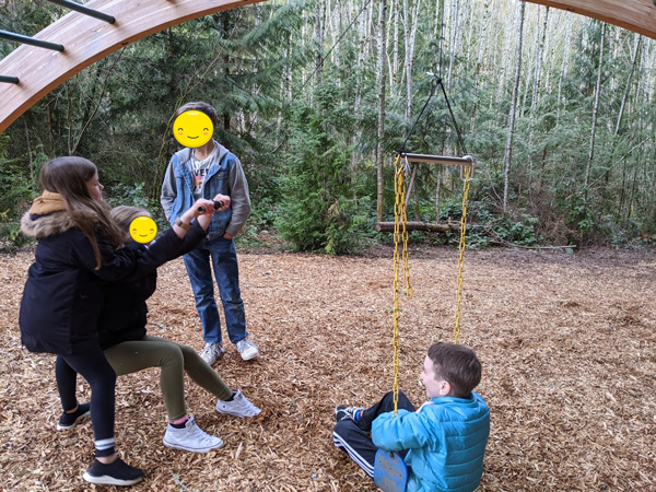 three students use a simple machine tied to a swing to lift