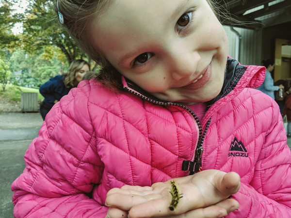 girl holds caterpillar that will become a butterfly