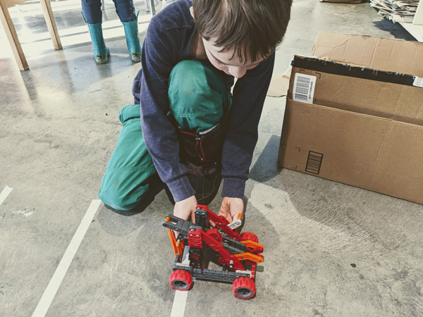 student works with a vex catapult